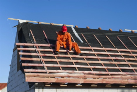 man sitting on roof under construction