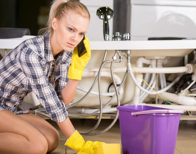 woman mopping up and calling to plumbing
